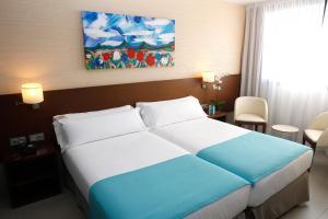 A bed or beds in a room at Hotel & Spa Real Ciudad De Zaragoza