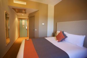 A bed or beds in a room at Ibis Ouarzazate
