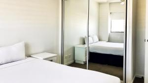 A bed or beds in a room at Oaks Townsville Gateway Suites