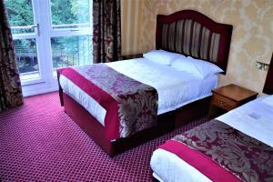 A bed or beds in a room at Buckatree Hall Hotel