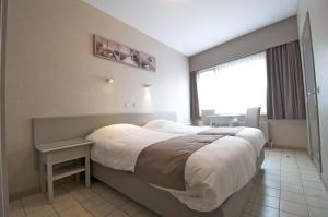 Ein Bett oder Betten in einem Zimmer der Unterkunft Hotel De Golf