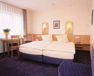 A bed or beds in a room at Hotel Sauer Garni