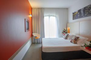 Letto o letti in una camera di iH Hotels Agrigento Kaos Resort