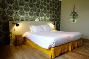 A bed or beds in a room at Hôtel & Spa Le Moulin de Moissac