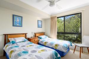 A bed or beds in a room at 2/80 Cooloola Drive - Comfortable and cosy unit enjoying ocean views and views to Fraser Island