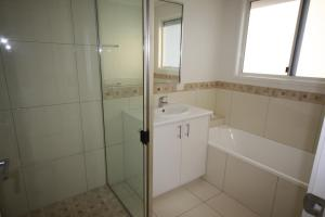 A bathroom at 62 Tingira Close - Modern lowset home with swimming pool, outdoor area, ample parking. Pet friendly