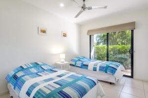 A bed or beds in a room at Unit 1 Rainbow Surf - Modern, two storey townhouse with large shared pool, close to beach and shop
