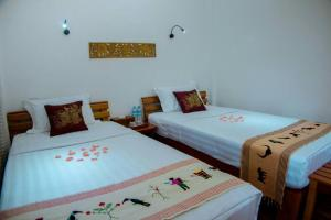 A bed or beds in a room at Mingalarpar Ngapali Guest House