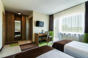 A bed or beds in a room at Mazurski Raj - Hotel, Marina & Spa
