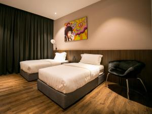 A bed or beds in a room at Eureka Hotel Penang