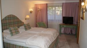 A bed or beds in a room at Pension Hartenfels
