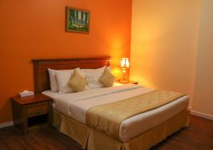 A bed or beds in a room at Al Maha Regency Hotel Suites