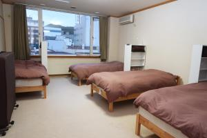 A bed or beds in a room at Otaru Ekimae Guest House Ito