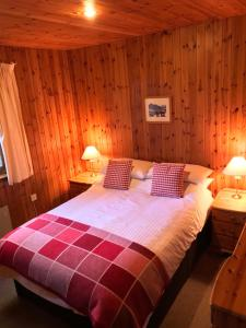 A bed or beds in a room at Tullochwood Lodges