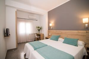 A bed or beds in a room at Hotel Abelay
