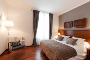 מיטה או מיטות בחדר ב-Serennia Apartamentos Ramblas - Plaça Catalunya