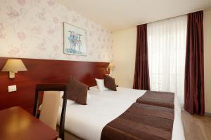 A bed or beds in a room at Hôtel Alane