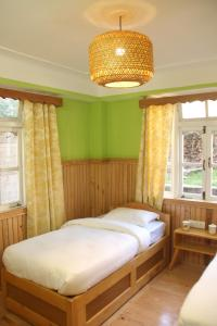 A bed or beds in a room at OurGuest Dhatup Homestay
