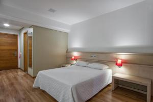 A bed or beds in a room at Alven Palace Hotel