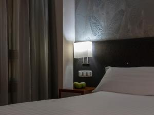 A bed or beds in a room at Hotel Plaza Las Matas