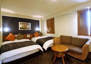 A bed or beds in a room at APA Hotel Miyazaki-eki Tachibana-dori