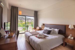 A bed or beds in a room at Rodon Hotel and Resort