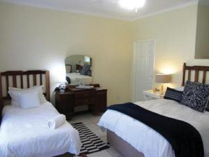 A bed or beds in a room at The Guest House Pongola