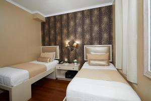 A bed or beds in a room at Belnord Hotel