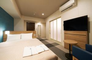 A bed or beds in a room at Sotetsu Fresa Inn Osaka Shinsaibashi
