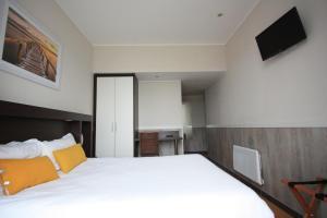 A bed or beds in a room at Hotel De La Rade