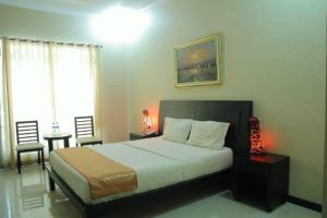 A bed or beds in a room at Jazz Hotel Palu