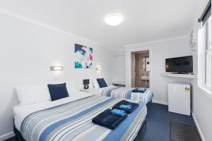 A bed or beds in a room at Wattle Grove Motel Maryborough