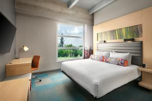 A bed or beds in a room at Aloft Miami Airport