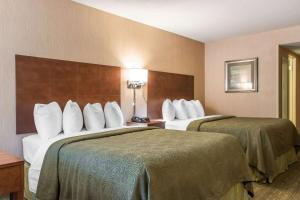 A bed or beds in a room at Quality Inn Bedford