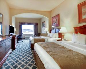 A bed or beds in a room at Clarion Suites Vidalia