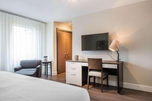 A television and/or entertainment center at Les Suites Victoria, Ascend Hotel Collection