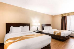 A bed or beds in a room at Quality Inn & Suites Orlando Airport