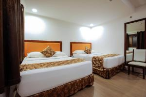 A bed or beds in a room at Paradise Garden Resort Hotel & Convention Center