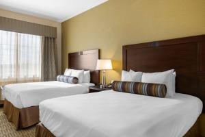 A bed or beds in a room at The Oaks Hotel & Suites, Ascend Hotel Collection