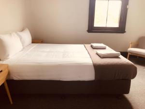 A bed or beds in a room at Empire Hotel Beechworth