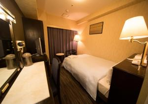 A bed or beds in a room at Hotel Claiton Esaka