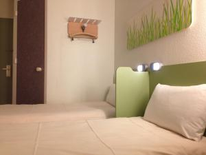 A bed or beds in a room at ibis Budget Caen Centre Gare