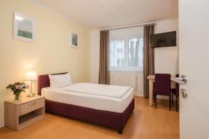 A bed or beds in a room at Hotel City Green Berlin