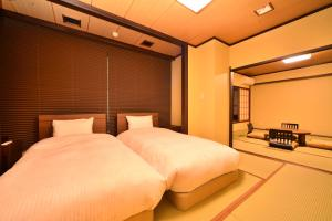 A bed or beds in a room at Hatago Kintoen