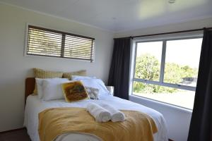 A bed or beds in a room at Waitomo Boutique Lodge