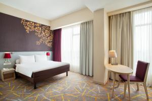 A bed or beds in a room at Ibis Styles Malang