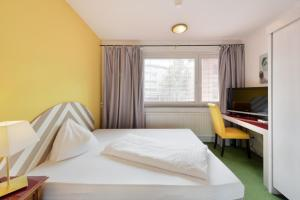 A bed or beds in a room at Am Neutor Hotel Salzburg Zentrum