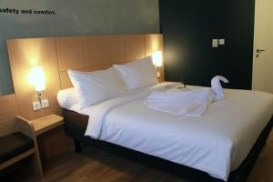 A bed or beds in a room at ibis Pontianak City Center