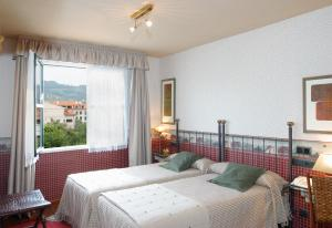 A bed or beds in a room at Hotel Avenida Real