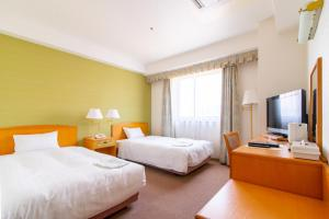 A bed or beds in a room at Bright Park Hotel